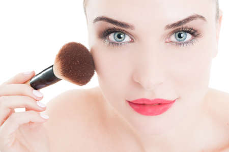 skintone: Woman using make-up brush on face cheeks and wearing cosmetics