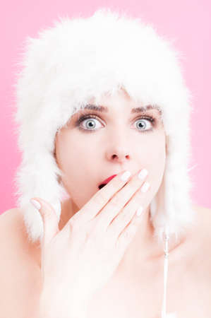 stupor: Astonished young woman wearing a white fur hat. Stock Photo