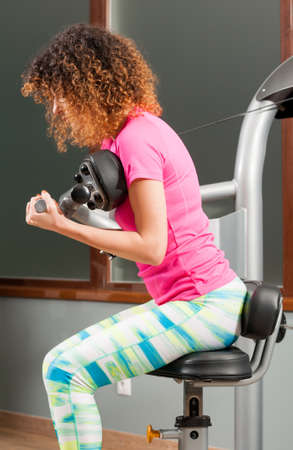 chest hair: Young woman exercising with abdominal machine as a healthy indoor activity Stock Photo