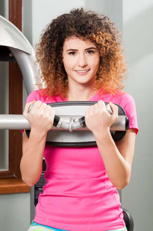 beautiful woman body: Attractive young woman smiling and doing workout in the gym Stock Photo