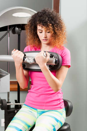 health woman: Woman doing biceps workout with exercising machine as workout concept