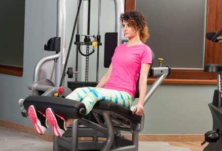 strengthen hand: Young female using lifting leg machine as workout concept