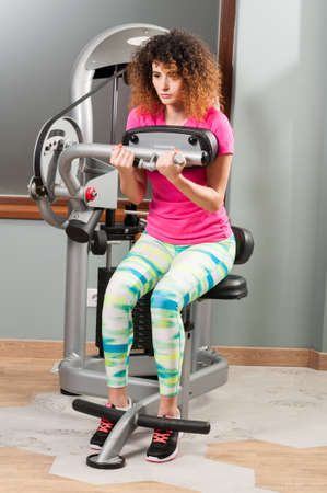 health woman: Beautiful curly female exercising for chest and arms at fitness club Stock Photo