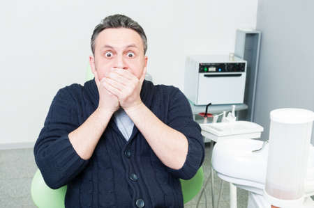 phobia: Frightened patient at dentist as dental phobia concept