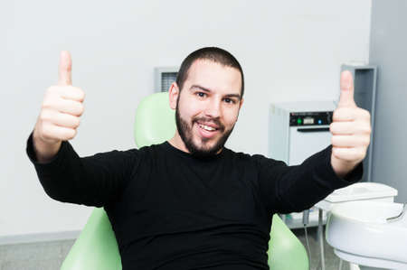 odontology: Cheerful and happy patient at dentist showing double like Stock Photo