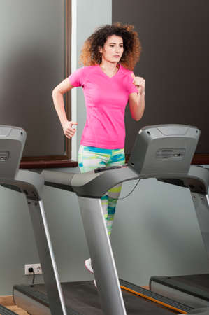 cardio workout: Beautiful woman running on treadmill in the gym as cardio workout concept