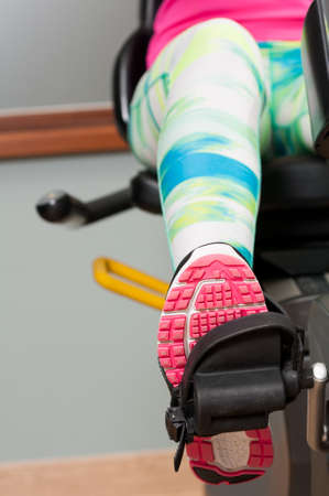 pedaling: Close-up of female leg wearing sport shoe and pedaling the stationary bike Stock Photo