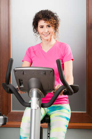 stationary bicycle: Beautiful woman smiling and using stationary bicycle in the gym