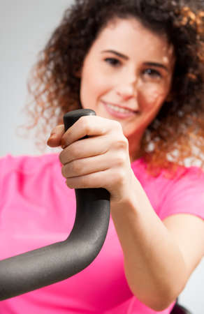 stationary bike: Beautiful female smiling and holding a stationary bike handle in the gym