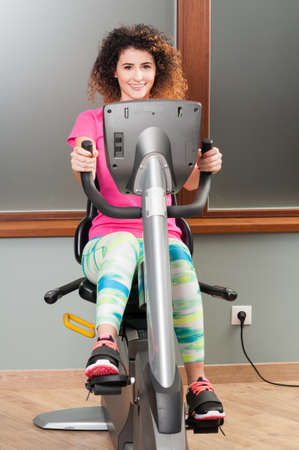 cardio workout: Attractive young female exercising on stationary bike and smiling as cardio workout concept