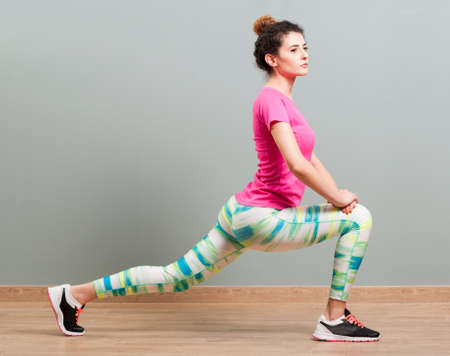 lunges: Attractive woman stretching and shaping her thighs by doing lunges in the fitness center