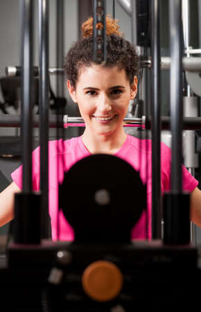 thru: Attractive female face thru gym equipment smiling and exercising as sporty lifestyle Stock Photo