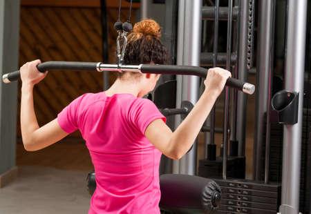 mujer joven el ejercicio con barra de gimnasio por la espalda en el gimnasio
