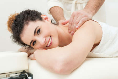 rejuvenate: Pretty young women smiling and relaxing in the spa and getting a rejuvenate massage