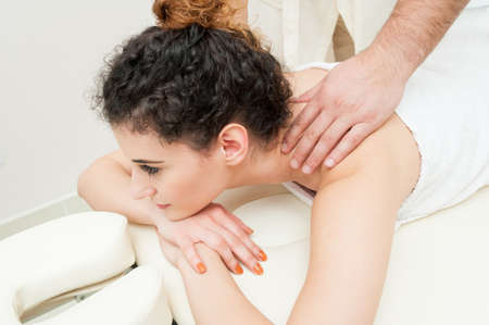 Beautiful female resting in beauty salon and getting spa massage by male masseur