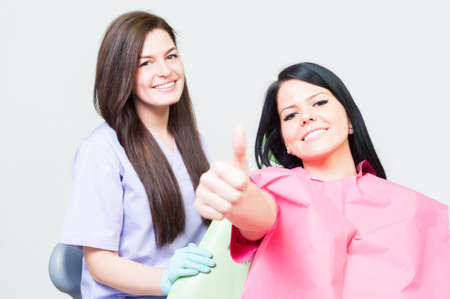 thumbup: Satisfied woman client at dentist showing like as approve gesture concept