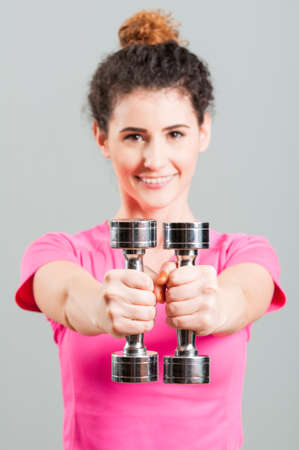 holding close: Sporty female holding close and doing arms exercises with dumbbells in the gym center Stock Photo