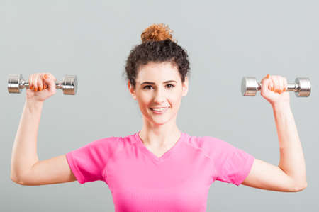 deltoid: Young smiling woman exercising for deltoid with dumbells in the gym as healthy lifestyle concept Stock Photo