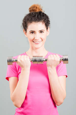 strenght: Yound woman doing weight training with dumbbells for arms strenght in the gym Stock Photo
