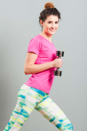 strengthen: Woman strengthen her biceps with chromed dumbbells in the gym as healthy indoor activity Stock Photo