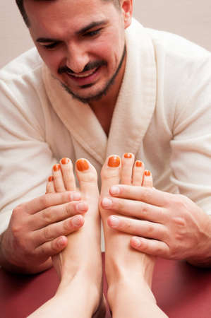 masseur: Attractive masseur smiling and massaging woman feet and soles as reflexology concept in the spa Stock Photo