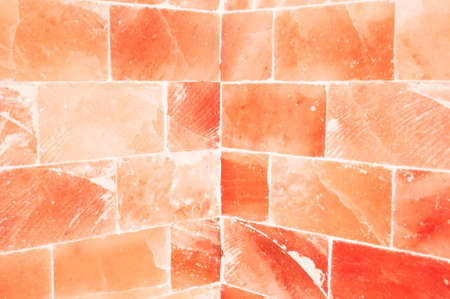 Close-up of orange salty wall inside sauna room as healty and energy concept