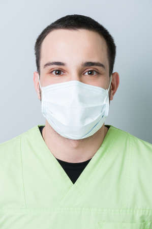 surgical mask: Male dentist wearing surgical mask portrait
