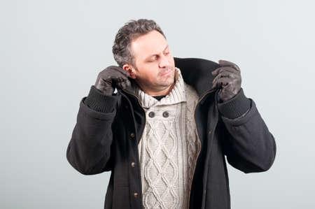 ropa de invierno: Var�n atractivo con guantes de cuero y ropa de invierno vestido de moda en fondo gris