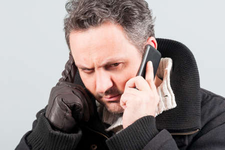 ropa de invierno: Close-up of frowning man in winter clothes talking on phone and wearing leather gloves