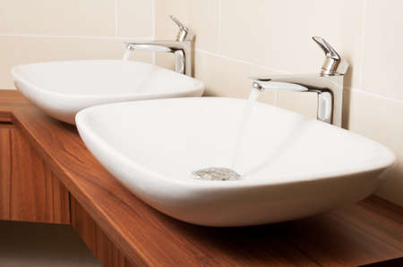 washbowl: Close-up of shiny taps with flowing water and ceramic sinks in a public washroom Stock Photo