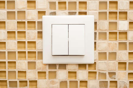 activating: Close-up of light switch on mosaic wall as modern technology concept