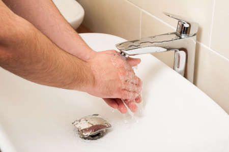 personal hygiene: Closeup of male hands being washed in white sink under running water as hygiene concept