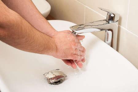 higiene: Primer de las manos masculinas que es lavado en el fregadero blanco con agua corriente como concepto de higiene