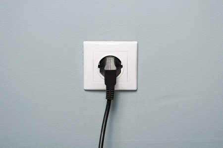 electrics: Closeup of electric socket with black cable plugged in as energy source concept