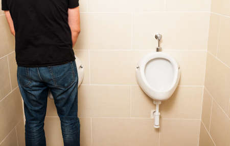 mensroom: Man standing in front of a white pissoir in a public modern bathroom