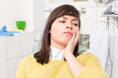 painfully: Young woman at the dentist with a tooth pain feeling uncomfortable