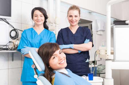 Portret van glimlachende vrouwelijke tandarts en assistent met vrouwelijke patiënt in de tandarts stoel als team werk concept
