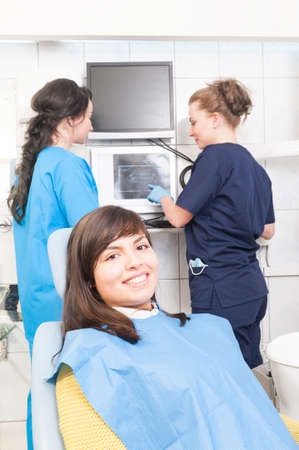 Female dentist and assistant analyzing dental x-ray plate at the dental clinic as oral radiography concept