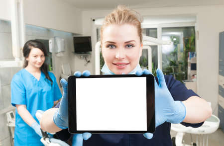 Young dentist using modern tablet with assistant in her back in dental clinic Standard-Bild