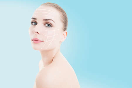 spotless: Beautiful woman with arrows on her perfect retouched face as cosmetic surgery concept against blue background
