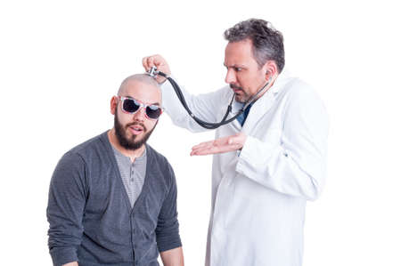 insane insanity: Young doctor checking a silly patient with head problem to establish a diagnostic on white studio background