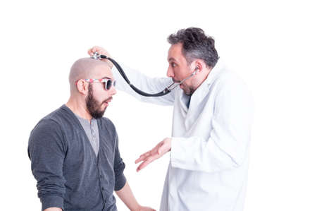 foolish: Young patient acting foolish during head examination on white background as insanity concept Stock Photo