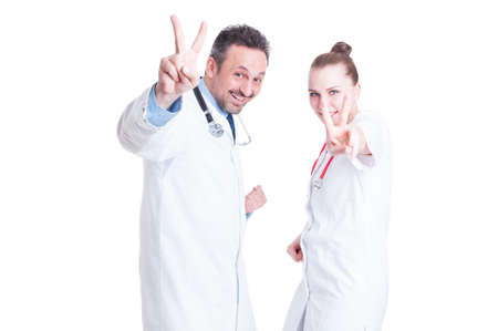 coworkers: Young joyful medical coworkers gesturing victory wearing white lab coats and smiling at the camera isolated on white background