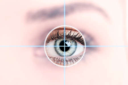 Close up of female blue eye scanned for access as high-tech personal identification concept