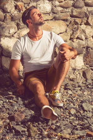 Fashion man in white t-shirt sitting down on stones and looking up