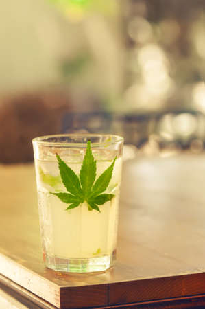 stimulant: Close-up of glass with ice, alcohol and marijuana leaf on a table as stimulant substance concept