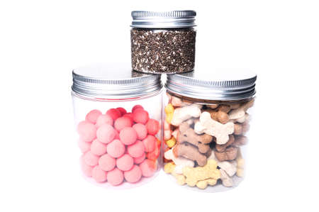 pet store advertising: Animal or pet food dry in transparent jars isolated as presentation on white studio background Stock Photo