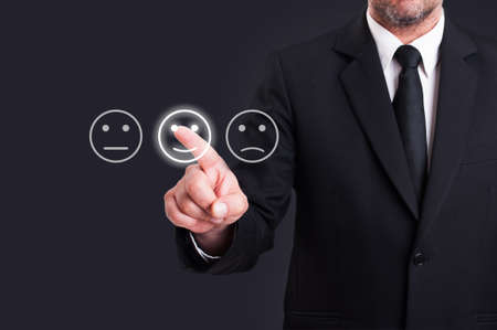 Businessman hand pointing the smiley face icon from screen as positive feedback concept against black background Standard-Bild