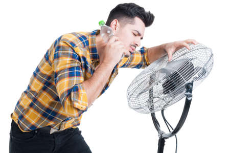 Sweaty and thirsty man standing near fan and cooling off on hot summer days isolated on white background