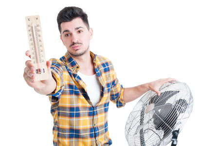 Attractive man with thermometer use electric fan to cool down during summertime isolated on white 免版税图像